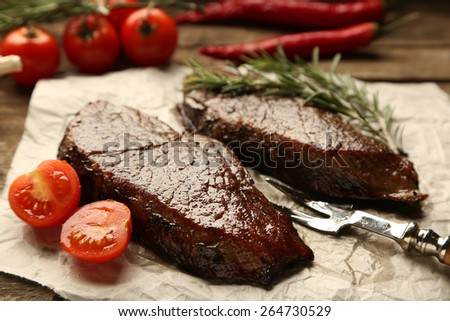 Composition with tasty roasted meat on paper sheet, tomatoes and rosemary sprigs on wooden background - stock photo