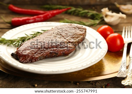 Composition with tasty roasted meat on plate, tomatoes and rosemary sprigs on wooden background - stock photo