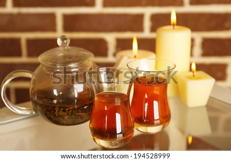 Composition with tea in cup and teapot and candles on table, on color wall background - stock photo