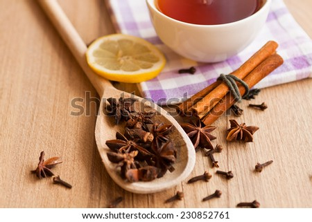 Composition with tea in cup, cinnamon, cloves and wooden background