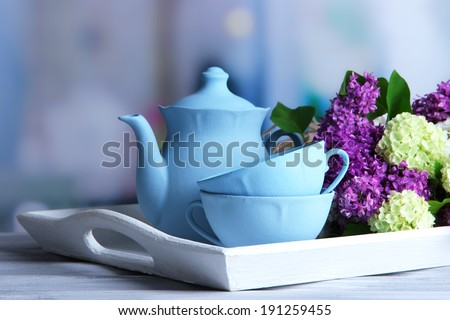 Composition with tea set and bouquet of beautiful spring flowers on tray, on wooden table, on bright background - stock photo
