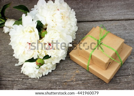 Composition with two presents decorated with simple brown craft paper and green jute and great bouquet of white peony on grey rustic background. Overhead view