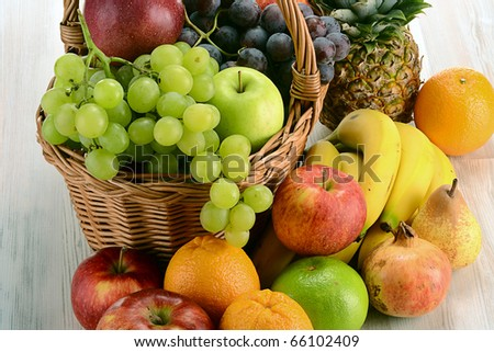 Composition with variety of fruits and wicker basket on kitchen table - stock photo