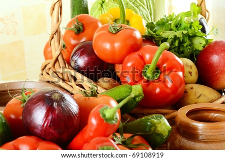 Composition with variety of raw vegetables and wicker basket