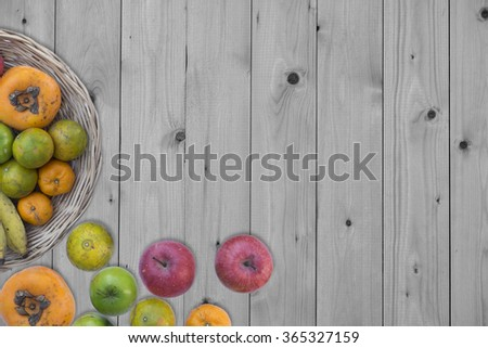 Composition with vegetables and fruits in wicker basket isolated on Wooden Background. - stock photo