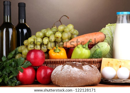 Composition with vegetables  in wicker basket on brown background