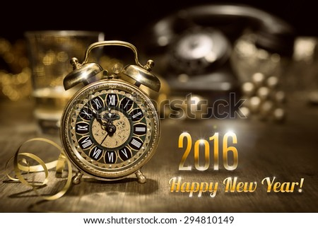 Composition with vintage alarm clock showing five to midnight and an old phone. Happy New Year 2016! - stock photo