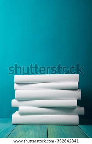 Composition with vintage old hardback books, diary, fanned pages on blue wooden deck table background. Books stacking. Back to school. Copy Space. Education background. - stock photo