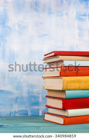 Composition with vintage old hardback books, diary, fanned pages on wooden deck table and red background. Books stacking. Back to school. Copy Space. Education background. - stock photo
