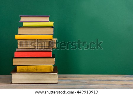 Composition with vintage old hardback books, diary on wooden deck table and green blackboard background. Books stacking. Back to school. Copy Space. Education background. - stock photo