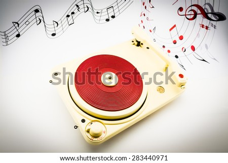composition with vintage red record player and musical notes on background - stock photo