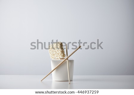 Compressed dry noodles brick presented on top of blank takeaway box with chopsticks isolated on white in center - stock photo