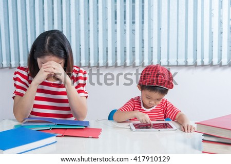 Computer addiction. Asian boy playing tablet and his mother frustrated.