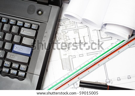 Computer and architect plans of housing project - stock photo