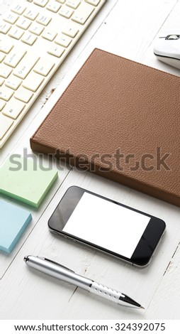 computer and brown notebook with office supplies on white table