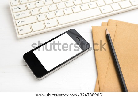 computer and cellphone with brown paper and pencil over white table