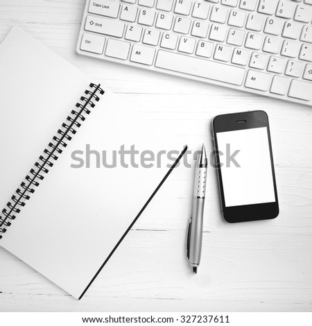 computer and cellphone with notebook and pen over white table black and white color style