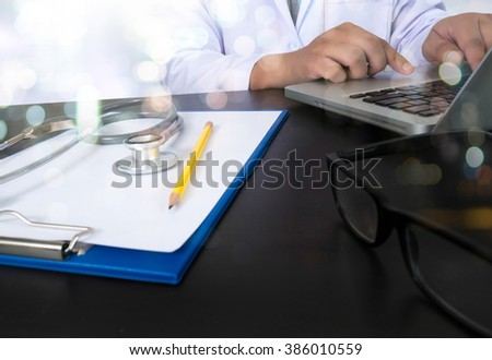 computer and digital pro tablet with digital medical diagram on wooden table medical concept, Medicine doctor hand working  Don't have an account? Get started for free. - stock photo
