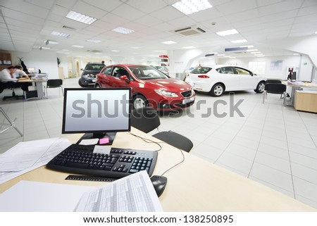 Computer and documents on wooden table and new cars stand in office of car shop. - stock photo