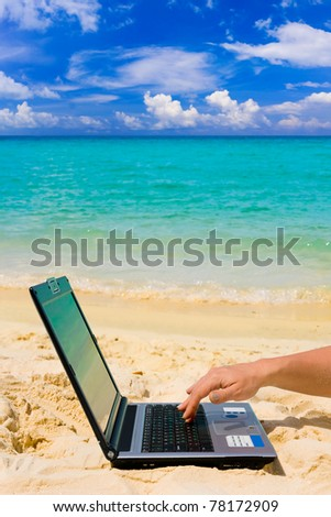 Computer and hand on beach, business travel background - stock photo