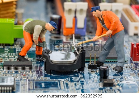 computer board and construction workers - stock photo