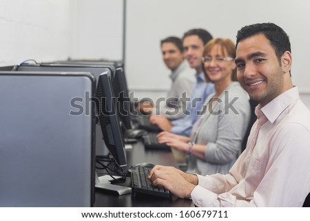 Computer class sitting in front of computers smiling at camera - stock photo