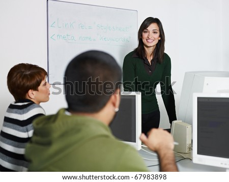 Computer class with caucasian female teacher talking to hispanic student. Horizontal shape, focus on background