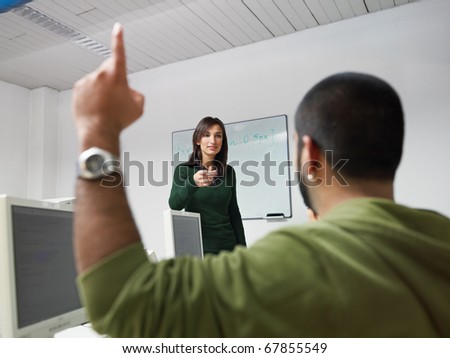 Computer class with hispanic student asking question to female teacher. Horizontal shape, focus on background - stock photo