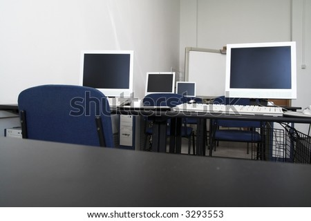 Computer classroom. Computers in row in school classroom - stock photo