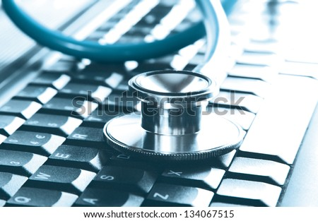 Computer concept of a stethoscope closeup on a computer keyboard (selective focus) - stock photo