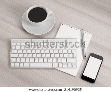Computer desk with a cup of coffee, a notebook and pen - stock photo
