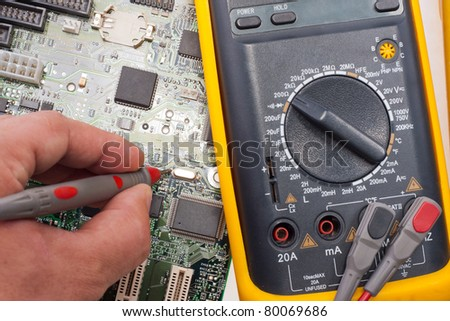 Computer engineer examining motherboard circuit by multimeter - stock photo