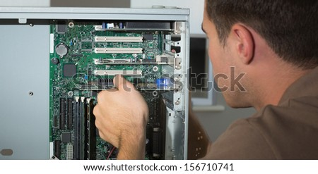 Computer engineer examining open computer in bright office