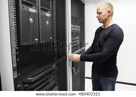 Computer Engineer Opening Server Rack Door In Data Center