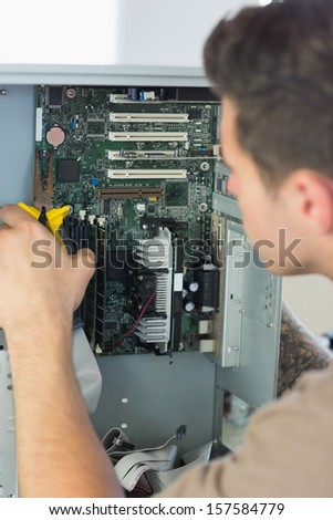 Computer engineer repairing open computer with pliers in bright office