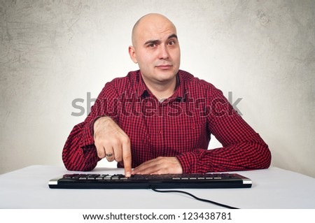 Computer expert sitting at the computer desk, pressing a computer key. - stock photo