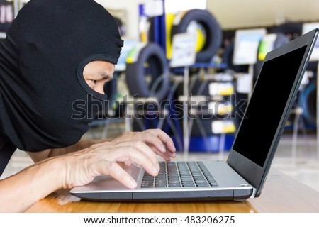 Computer hacker, blur image of inside the tire shop as background.