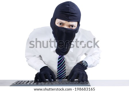 Computer hacker - businessman wearing mask stealing data from computer. - stock photo