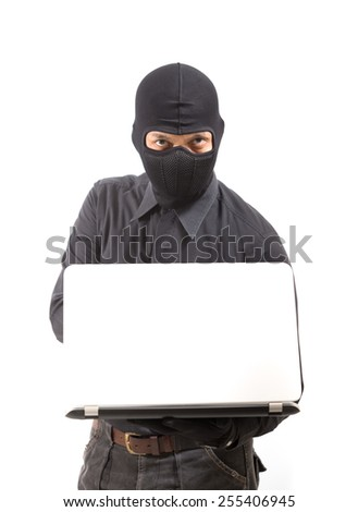 Computer hacker - businessman wearing mask stealing data from computer. Isolated white background - stock photo