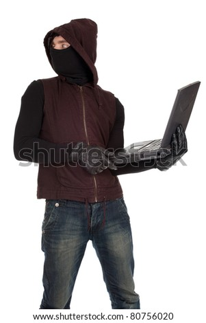 computer hacker - criminal in balaclava with the laptop - stock photo