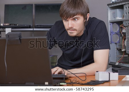 computer hacker in black shirt working at laptops - stock photo