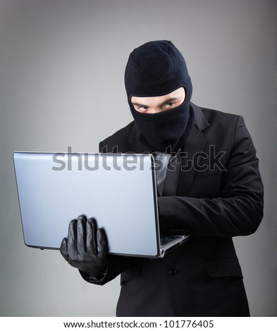 Computer Hacker in suit and tie stealing data from laptop computer, isolated on white