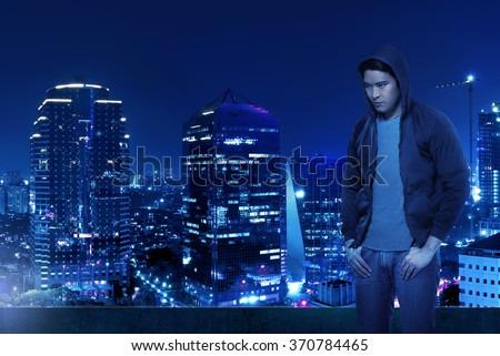 Computer hacker silhouette of hooded man standing on the top of the building at night - stock photo