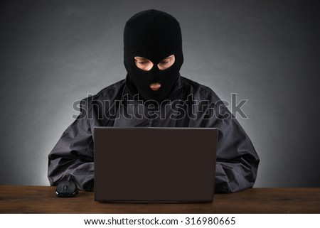 Computer Hacker Stealing Data From A Laptop At Desk - stock photo