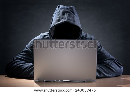 Computer hacker stealing data from a laptop concept for network security, identity theft and computer crime - stock photo