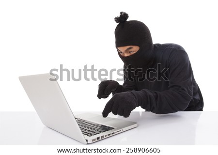 Computer hacker wearing mask stealing data on laptop computer  - stock photo