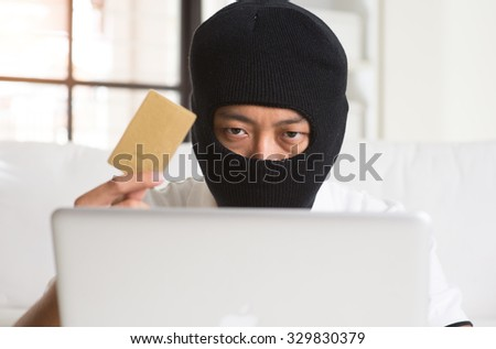 computer hacker with credit card and laptop - stock photo