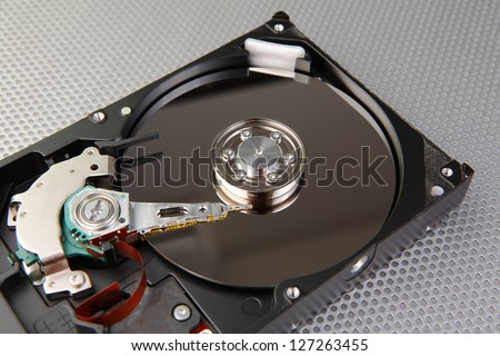 Computer hard disk drive detail with interesting technology background, focused to center of plate