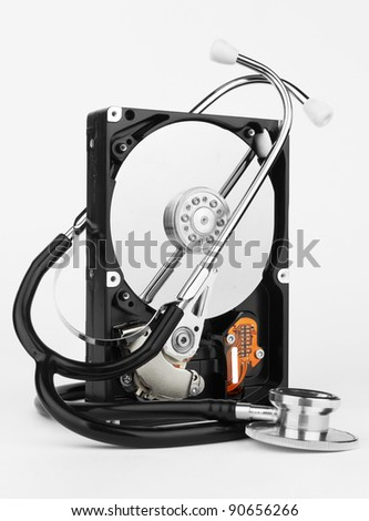 Computer hard drive and a stethoscope, on white background - stock photo
