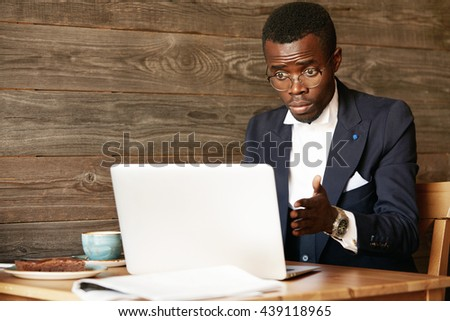 Computer keeps freezing! Human face expressions and emotions. Shocked African American businessman looking at his laptop with shock and indignation, shaking his hand with surprise and disappointment - stock photo